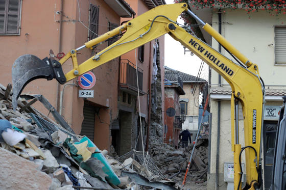 An excavator digs through rubble of collapsed buildings following an earthquake, in Amatrice, Italy, Wednesday, Aug. 24, 2016.  The magnitude 6 quake struck at 3:36 a.m. (0136 GMT) and was felt across a broad swath of central Italy, including Rome where residents of the capital felt a long swaying followed by aftershocks.