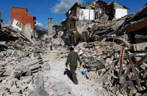 A man walks amidst rubble following an earthquake in Pescara del Tronto, central...