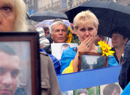 People hold photos of their relatives who were killed as soldiers in the conflict with pro-Russian separatists in the country's east, as they attend a rally for Independence Day in the Ukrainian capital Kiev, Wednesday, Aug. 24, 2016. (AP Photo/Efrem Lukatsky)
