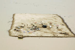 Villagers wave from their settlement as they are seen surrounded by flood water near Shahdad Kot July 3, 2007. Thousands of people in three districts of the usually desert-like Baluchistan province remained cut off, a week after a cyclone brought rains and severe flooding to the region.
