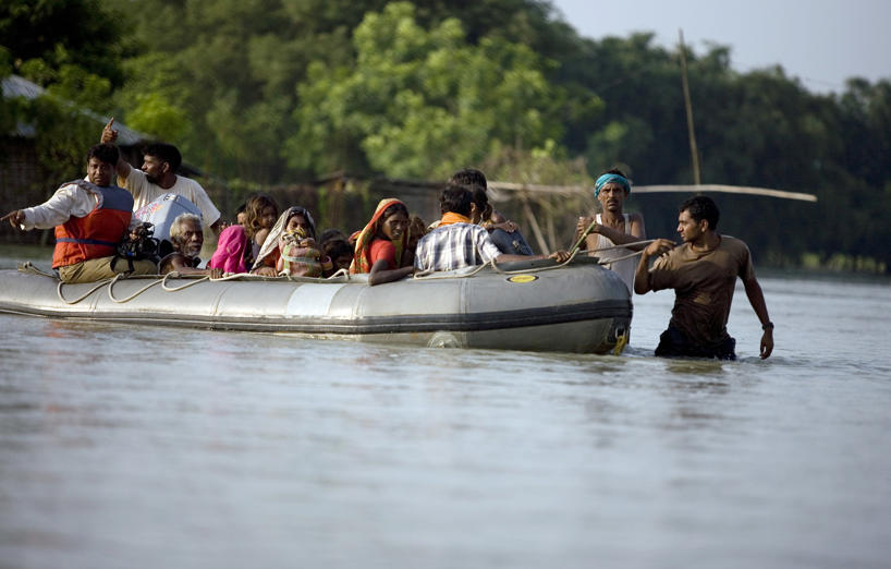 A navy personell pulls a boat as he rescue flood victims marooned for the past15 days after the Kosi river flooded in Purnea Dist, Bihar, India, on Wednesday, Sep. 3, 2008.