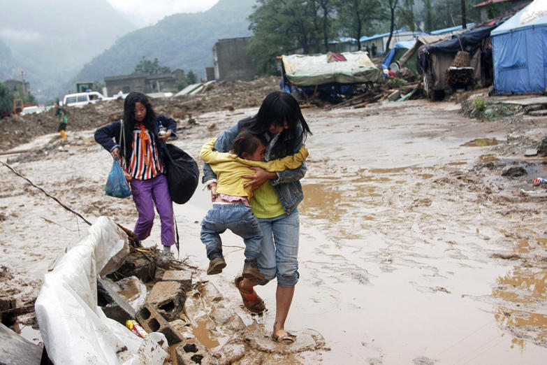A woman holding her daughter crosses a muddy road after a flash flood caused by torrential rain hit Beichuan, Sichuan province September 25, 2008. Sixteen people have died and 48 others are missing after flash floods and landslides hit an area of southwest China still recovering from a devastating earthquake in May, state media said on Friday. Picture taken September 25, 2008.