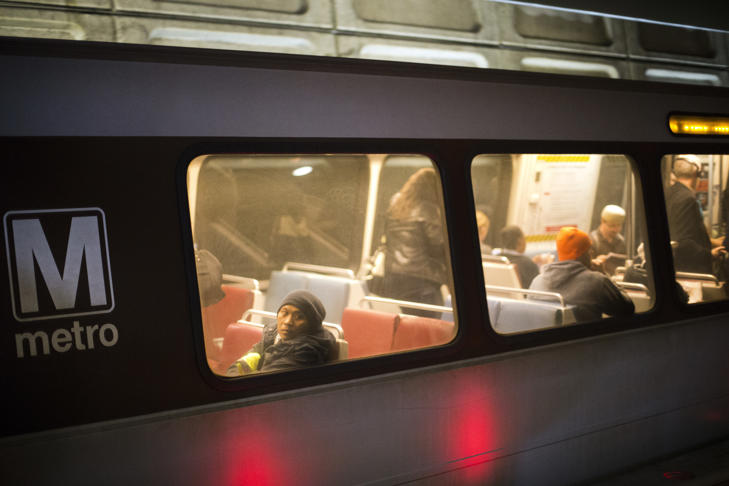 In this photo taken Nov. 16, 2015, passengers ride a Washington Metro subway train at the Chinatown Metro Station in Washington. Authorities say a Washington, D.C.-area transit police officer has been charged in an FBI sting with attempting to support the Islamic State group.