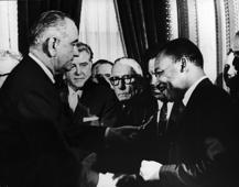 U.S. President Lyndon B. Johnson hands a pen to civil rights leader Rev. Martin Luther King Jr. during the the signing of the voting rights act as officials look on behind them, Washington, D.C., August 6, 1965.