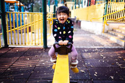 Toddler girl playing on the seesaw