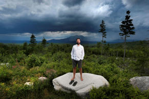 In this Aug. 4, 2015 photo, Lucas St. Clair, the son of Burt's Bees founder Roxanne Quimby, poses on land proposed for a national park in Penobscot County, Maine. Mount Katahdin, the state's highest peak, can be seen in the background as a rainstorm passes through Baxter State Park. President Barack Obama on Wednesday, Aug. 24, 2016 declared a new national monument in Maine on 87,000 acres donated by Quimby, fulfilling the conservationist's goal of gifting the land during the 100th anniversary of the National Park Service. (AP Photo/Robert F. Bukaty, File)
