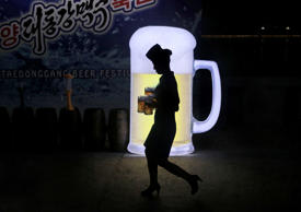 A waitress is silhouetted against an advertisement board as she carries jugs of beer during Taedonggang Beer Festival in Pyongyang, North Korea, Sunday, Aug. 21, 2016. The festival, the first of its kind in the country, was held as a promotional event fo