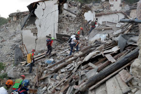 Rescuers search through debris following an earthquake in Pescara Del Tronto, It...
