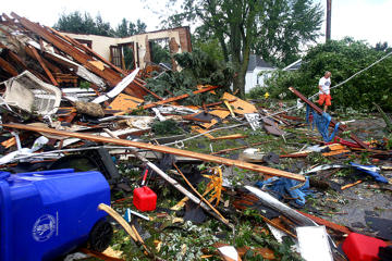 A man walks through debris after a tornado in Kokomo, Ind., Wednesday, Aug. 24, 2016. Multiple tornadoes touched down in central Indiana on Wednesday, tearing the roofs off apartment buildings, sending air conditioners falling onto parked cars and cutting power to thousands of people.