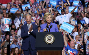 Democratic presidential candidate Hillary Clinton addresses a gathering at a campaign rally Monday, Aug. 15, 2016, in Scranton, Pa., as Vice President Joe Biden applauds.