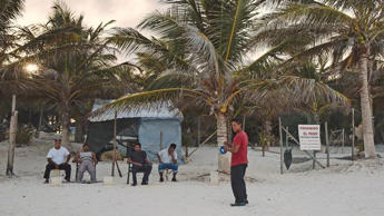 Men armed with machetes guard a beachside property that was seized in Tulum, Mexico, Aug. 12, 2016.
