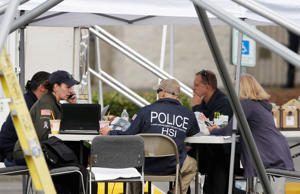 Law enforcement officials work under a tent, Saturday, Sept. 24, 2016, outside the Cascade Mall in Burlington, Wash. Friday night, a man with a rifle opened fire in a Macy's Department Store at the mall, killing several people.