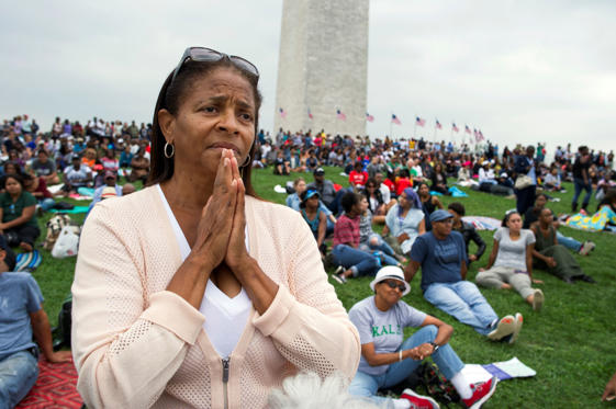 Giselle Shapiro of Los Angeles, holds her hands in prayer on the Washington Monument grounds in Washington, Saturday, Sept. 24, 2016, as she listens to President Barack Obama speak at the dedication and opening ceremony of the Smithsonian's National Muse