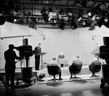 At the first televisied presidential debate, American then-senator and future President John F. Kennedy (1917 - 1963) (on stage at left) speaks while then-Vice President and future President Richard Nixon (1913 - 1994) (right) and journalist and debate chairman Howard K. Smith (1914 - 2002) (on stage, seated in center) listen, Chicago, Illinois, September 25, 1960.