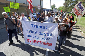 Protesters march outside the Great Faith Ministries International church, Saturday, Sept. 3, 2016, in Detroit, where Donald Trump visited with the church members.