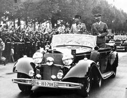 German Chancellor Adolf Hitler, right, and Italian leader Benito Mussolini stand in the back of a car on their journey from the Heerstrasse Station to the Hindenburg Palace, in Berlin, Sept. 27, 1937. Three quarters of a million people lined the route to cheer the two leaders.