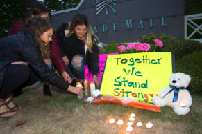 Ariel Pantoja, 19, Bayley Morrow, 18 and Makayla Bentley, 18, light candles at a makeshift memorial outside the Cascade Mall on September 24, 2016 in Burlington, Washington.