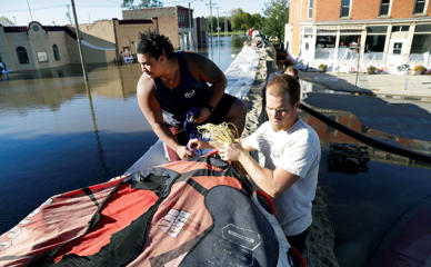 (From left) Cory Harrison & Josh Jensen climb over a flood wall after helping a friend with a business flooded by the Cedar River on Tuesday in Cedar Rapids, Iowa.