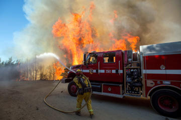 Flames from a wildfire tower above a firefighter as he tries to stop the blaze from crossing Loma Prieta Ave. near Morgan Hill, Calif., on Sept. 27.