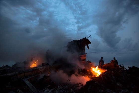People walk amongst the debris at the crash site of a passenger plane near the village of Hrabove, Ukraine, on July 17, 2014.