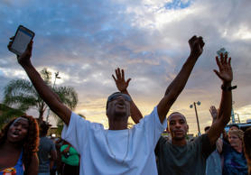People yell toward police at the scene where a black man was shot by police earl...