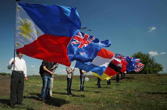 People hold national flags of countries of the passengers who were killed at the crash site of the Malaysia Airlines Flight 17, near the village of Hrabove, eastern Ukraine on July 17, 2015.