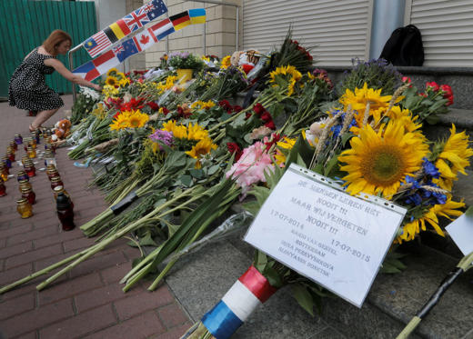 People lay flowers at the Netherlands Embassy for the Malaysia Airlines Flight MH17 crash victims, in Kiev, Ukraine, on July 17, 2015.