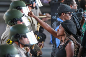 "Ebonay Lee holds up her fist toward a line of Sheriff's deputies as she and other people protest Wednesday, Sept. 28, 2016, in El Cajon, Calif. Dozens of demonstrators protested the killing of a black man shot by an officer after authorities said the man pulled an object from a pocket, pointed it and assumed a ""shooting stance."""