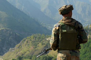 An Indian army soldier looks towards the site of a gunbattle between Indian army soldiers and rebels inside an army brigade headquarters near the border with Pakistan, known as the Line of Control (LoC), in Uri on September 18, 2016.
