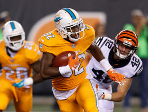 Miami Dolphins running back Kenyan Drake (32) carries the ball as Cincinnati Bengals' Clayton Fejedelem pursues during the first half of an NFL football game Thursday, Sept. 29, 2016, in Cincinnati.