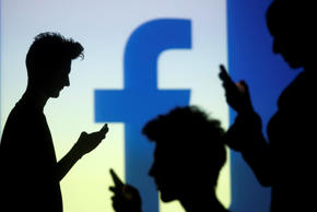 In the file picture, people are silhouetted as they pose with mobile devices in front of a screen projected with a Facebook logo.