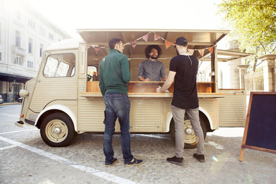 Slide 1 of 12: A man sells mexican food to customers out of a food truck