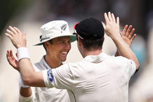 New Zealand's Trent Boult, left, celebrates with teammate Matt Henry after taking the wicket of Indian batsman Mohammed Shami on the second day of the second cricket test match, in Kolkata, India, Saturday, Oct. 1, 2016.