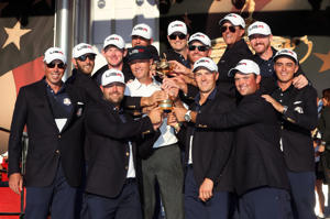The USA team celebrate with the Ryder Cup after they won, on day three of the 41st Ryder Cup at Hazeltine National Golf Club in Chaska, Minnesota, USA.