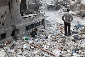 A Syrian boy collects items amidst the rubble of destroyed buildings on October 3, 2016, following reported air strikes in the rebel-held town of Douma, on the eastern outskirts of the capital Damascus.