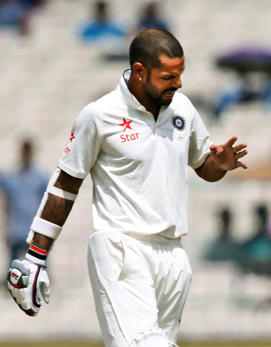 Shikhar Dhawan looks at his finger after getting hurt on the third day of the second cricket test match against New Zealand.