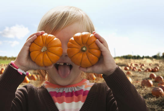 Slide 1 of 12: Caucasian girl covering eyes with small pumpkins KidStock