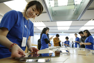 An employee, left, arranges an Apple Inc. iPad Air tablet while other employees help customers purchase the devices at the Apple Store Ginza in Tokyo, Japan, on Friday, Nov. 1, 2013.
