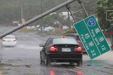 A car drives past a collapsed traffic sign, toppled by strong winds of typhoon Meranti, in Kaohsiung, Taiwan, Sept. 14, 2016.