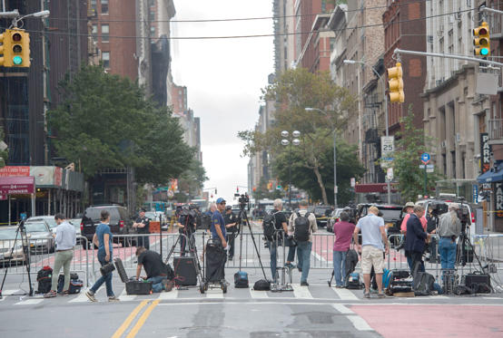 The media are lined up behind a barrier at the scene, following an explosion on West 23rd Street September, 18, 2016 in New York. An  explosion rocked one of the most fashionable neighborhoods of New York on September 17 night, injuring 29 people, one seriously, a week after America's financial capital marked the 15th anniversary of the 9/11 attacks. Mayor Bill de Blasio indicated the blast was not accidental, even if there was no known link to terrorism. The blast occurred in Chelsea -- an area packed with bars, restaurants and luxury apartment blocks -- at a typically bustling time of the weekend.
