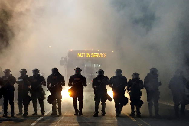 Police officers wearing riot gear block a road during protests after police fatally shot Keith Lamont Scott in the parking lot of an apartment complex in Charlotte, North Carolina, U.S. September 20.