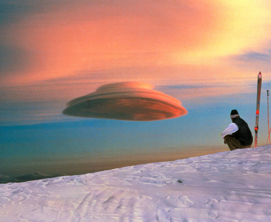 Lenticular cloud. Skier looks at a lenticular cloud or altocumulus lenticularis. These clouds get their name from their smooth, lens-like shape. They are usually caused when wind forms standing waves of air on the lee side of mountains. Lenti- cular clou