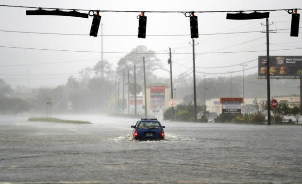 A motorist drives through a flooded street from Hurricane Matthew in Brunswick, Ga., Oct. 7, 2016.