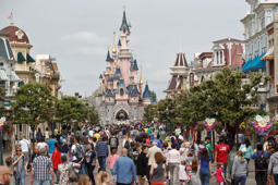 FILE - In this May 12, 2015, file photo, visitors walk near Sleeping Beauty's Castle at Disneyland Paris, in Marne la Vallee, east of Paris. Disney brought its vision of Americana to France with the opening of Disneyland Paris and Walt Disney Studios Park in 1992. To please France, French is the main language for the park, which includes French and European-themed attractions. Mickey and Donald retained their names, but Goofy is called Dingo and Snow White and the Seven Dwarfs are Blanche Neige et Les Sept Nains. (AP Photo/Michel Euler, File)