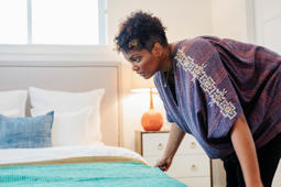 woman smoothing a throw over a double bed in a bedroom.