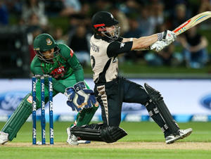 Kane Williamson of New Zealand bats while Nurul Hasan Sohan of Bangladesh looks on during the first Twenty20 match