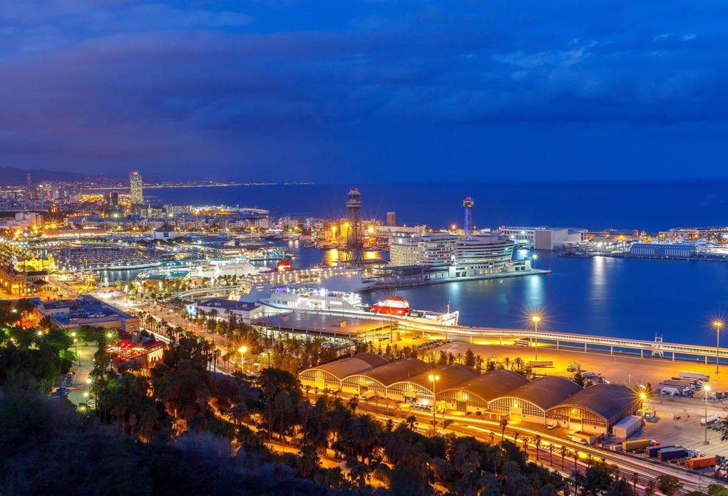 View of Barcelona and the sea port with Montjuk hill at sunset.