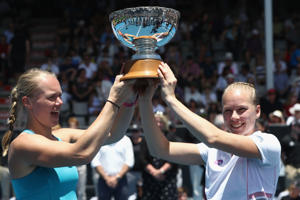 Kiki Bertens of the Netherlands (L) and Johanna Larsson of Sweden (R) hold the trophy after winning the womens doubles final.