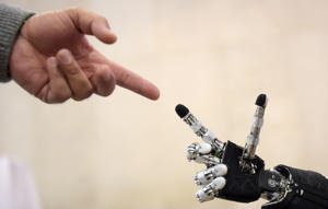 A man moves his finger toward the finger of humanoid robot iCub during the 2014 IEEE-RAS International Conference on Humanoid Robots in Madrid on November 18, 2014. The iCub is the humanoid robot developed at IIT (Instituto Italiano di Tecnologia) as part of the EU project RobotCub and subsequently adopted by more than 20 laboratories worldwide. It has 53 motors that move the head, arms & hands, waist, and legs. It can see and hear, it has the sense of proprioception (body configuration) and movement (using accelerometers and gyroscopes). The conference theme 'Humans and Robots Face-to-Face' confirms the growing interest in the field of human-humanoid interaction and cooperation, especially during daily life activities in real environments.