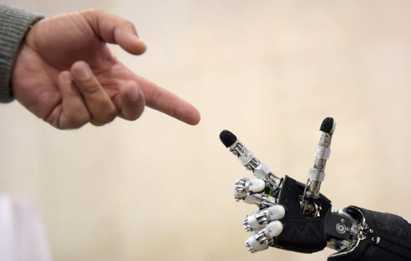 Folie 1 von 28: A man moves his finger toward the finger of humanoid robot iCub during the 2014 IEEE-RAS International Conference on Humanoid Robots in Madrid on November 18, 2014. The iCub is the humanoid robot developed at IIT (Instituto Italiano di Tecnologia) as part of the EU project RobotCub and subsequently adopted by more than 20 laboratories worldwide. It has 53 motors that move the head, arms & hands, waist, and legs. It can see and hear, it has the sense of proprioception (body configuration) and movement (using accelerometers and gyroscopes). The conference theme 'Humans and Robots Face-to-Face' confirms the growing interest in the field of human-humanoid interaction and cooperation, especially during daily life activities in real environments.
